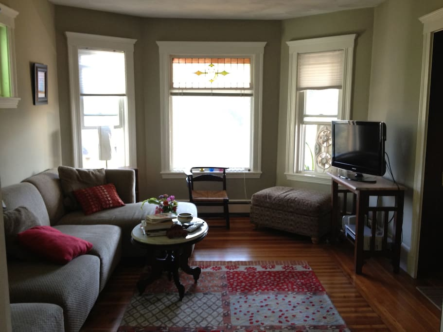 A living room with pretty windows and comfortable seating and TV.