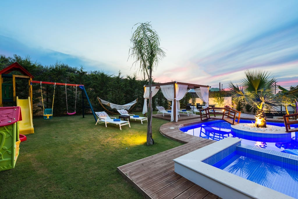 Lawn covered garden and wooden deck around the pool!