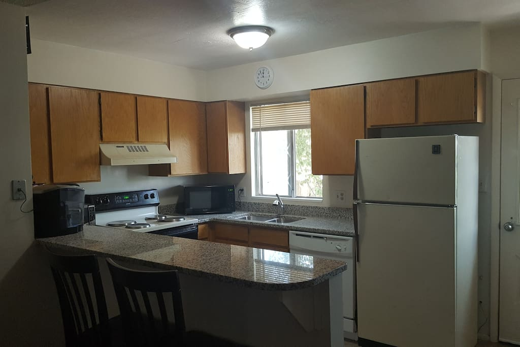 Kitchen has a microwave, stove, fridge, toaster oven, and Keurig coffee maker.