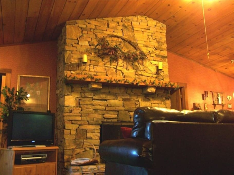 Living room with imposing stack stone wood burning fireplace