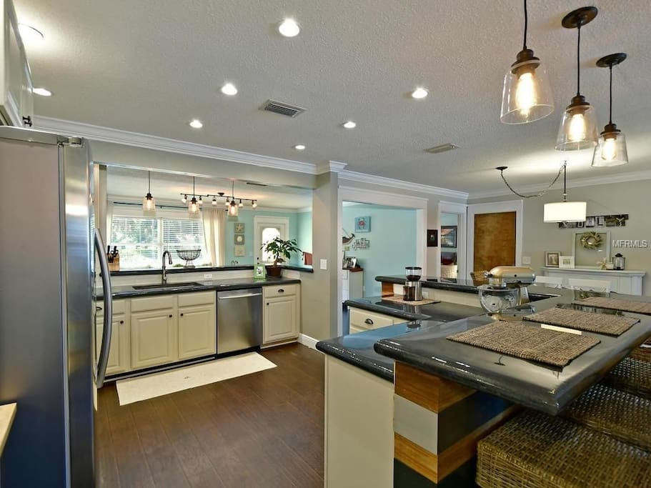 Stunning kitchen with multiple eating stations, SS appliances. Note: the mixer in the photos is not avl anymore. The bar wicker bar chairs are different as well.