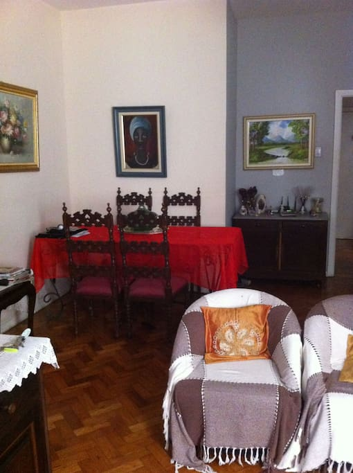 Sala ampla, mobiliada, com televisão, mesa jantar, sofá e poltronas