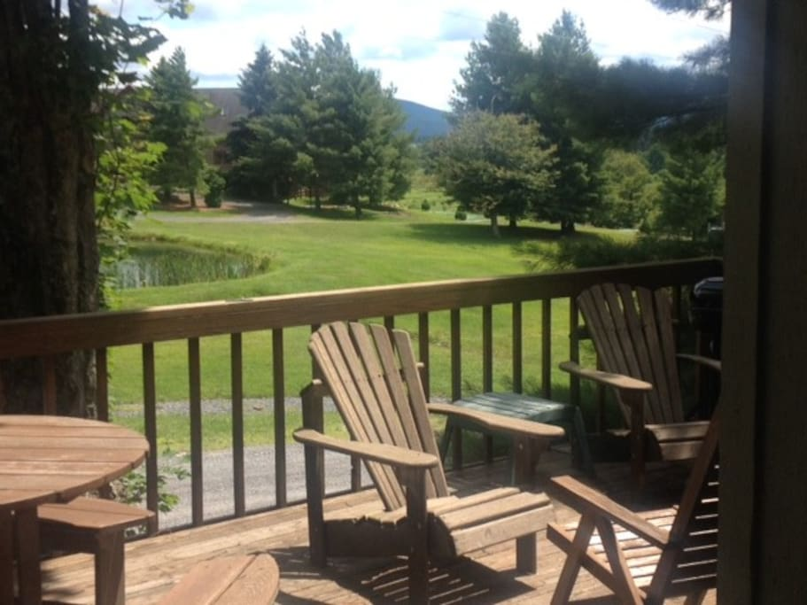 The deck, with a serene view of the pond and mountains.