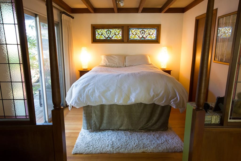 Bedroom with sliding doors to the deck and stained glass windows.  There is a twin bed under this queen platform that can be pulled out and put on the floor to accommodate another person.