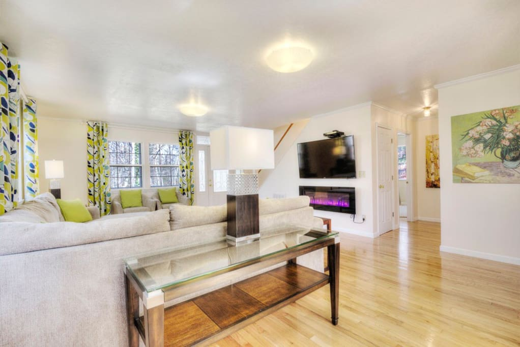 """Living room downstairs with 60"""" TV and electric fireplace with different settings"""