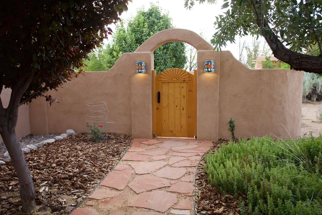 Lighted gate to the back yard leading to La Casita.