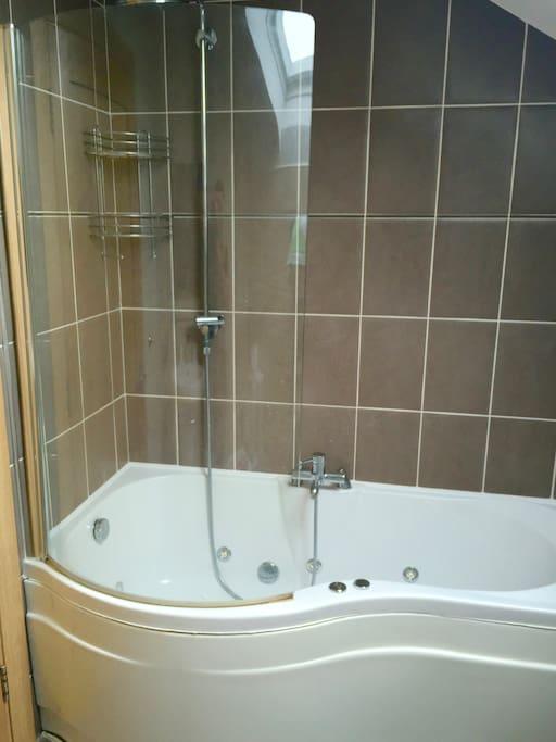 Bathroom with jacuzzi bath and rain shower.