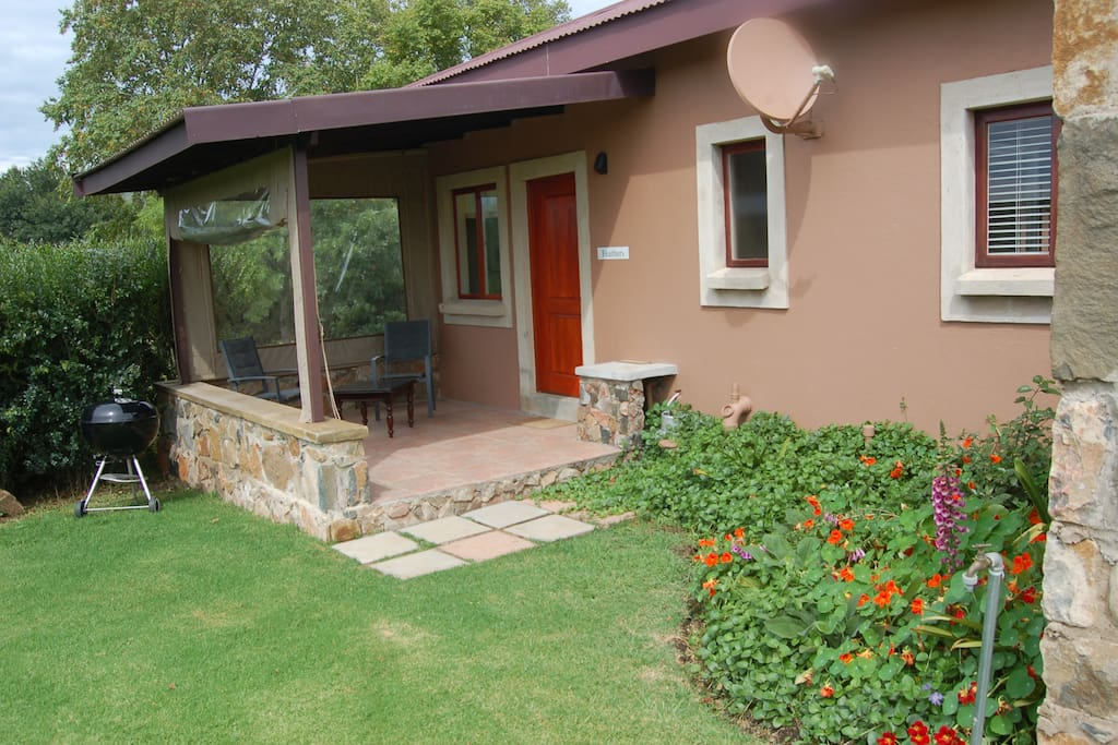 Entrance covered stoep with drop down blinds, braai, and garden