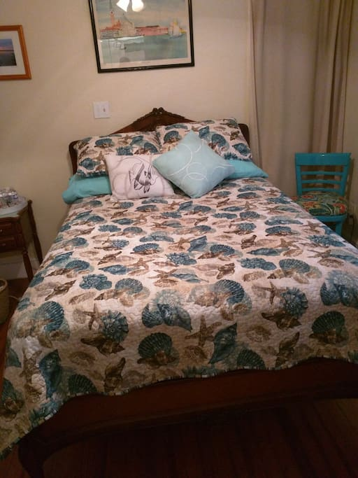 Full size, comfortable bed in coastal decorated room with private bath.