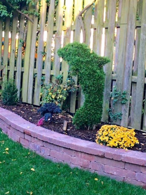 A serene Topiary Garden with a Patio, BBQ Grill and Outdoor Dining Furniture