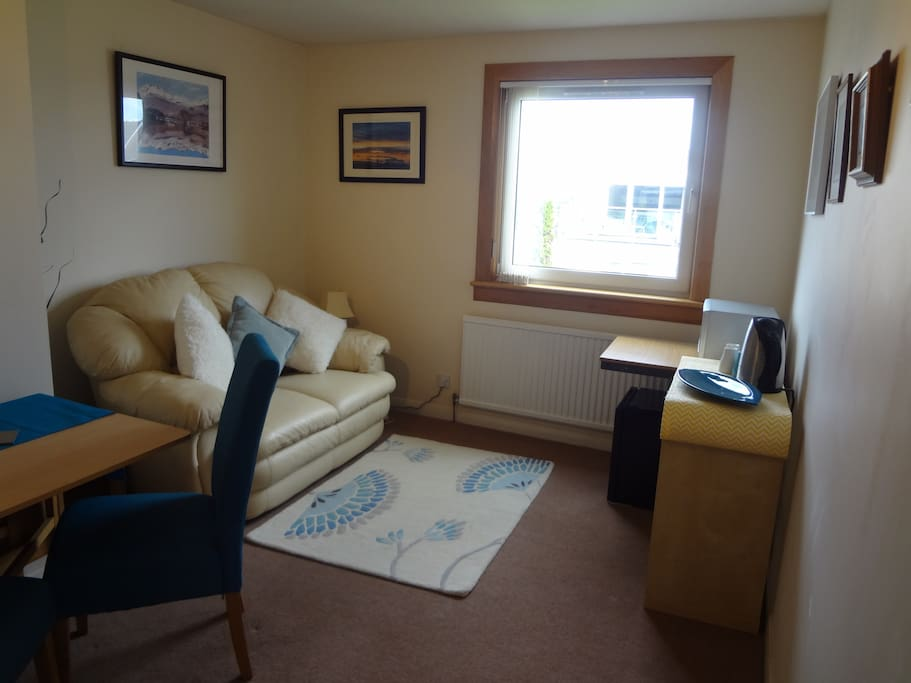Living and dining area, includes microwave and kettle.