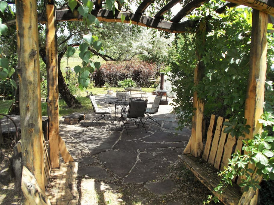 Luscious back yard with a variety of flowering plants and other greenery.  Includes seating and outdoor dining/fireplace amenities.