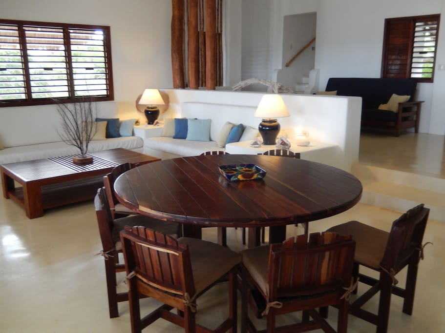 Spacious, light open-plan living room with dining seating for 8
