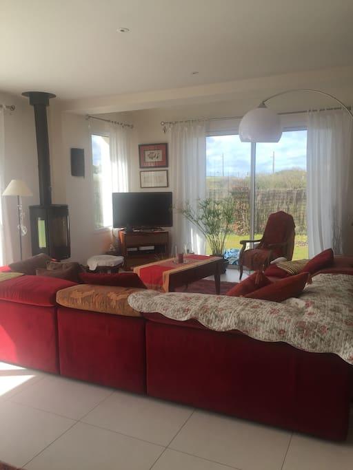 Grand salon chaleureux et très confortable.