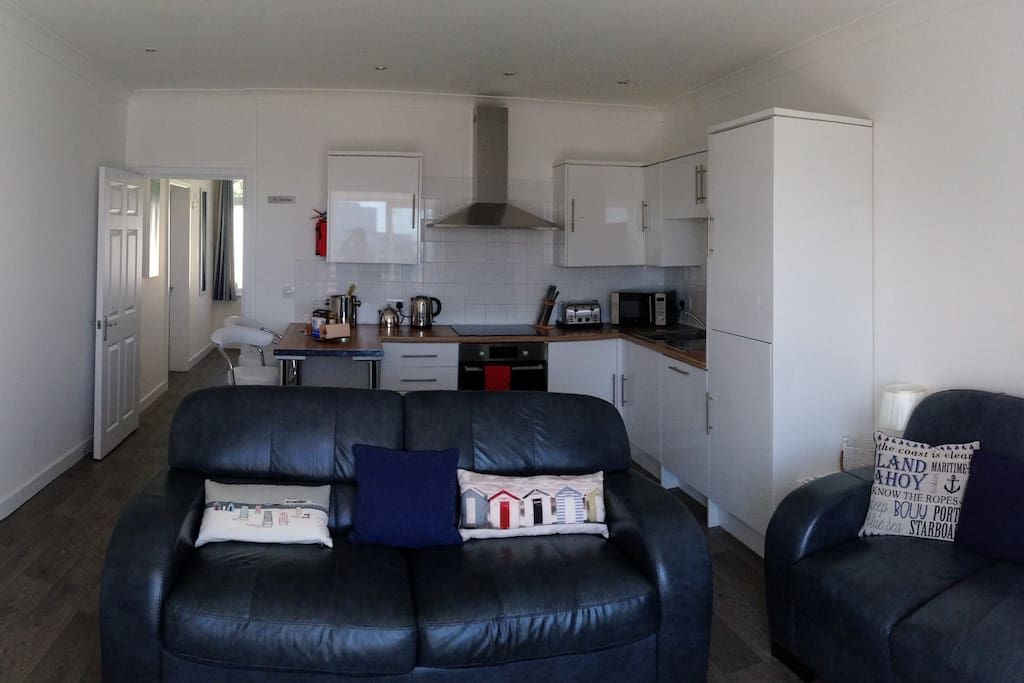 The main living room with leather sofas, kitchen and breakfast bar