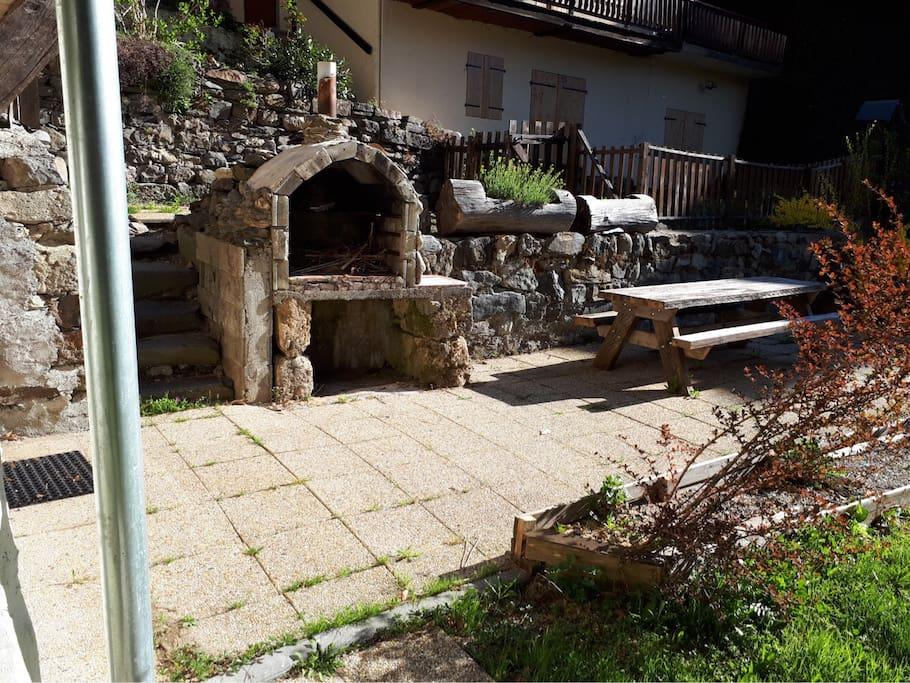 Terrasse avec barbecue en pierre et table de jardin